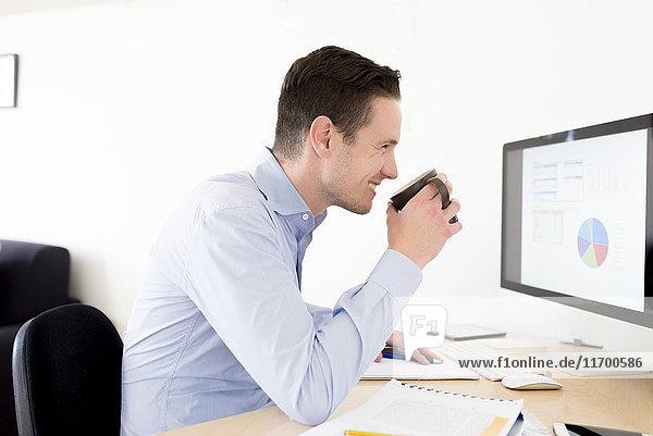 Lächelnder Geschäftsmann mit einer Tasse Kaffee  der das Kuchendiagramm auf dem Computerbildschirm analysiert.