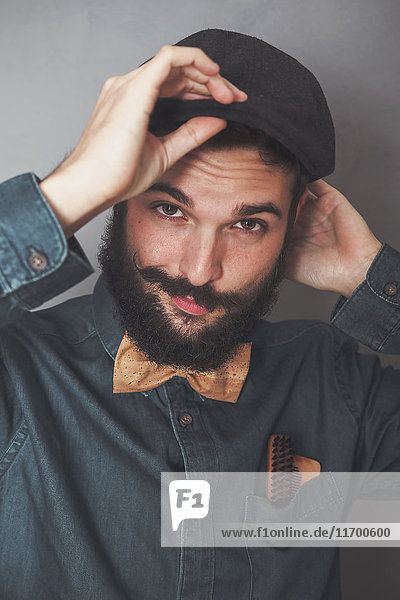 Portrait of bearded man wearing cap  denim shirt  cork bow tie  wearing wooden combs for beard and mustache in his pocket