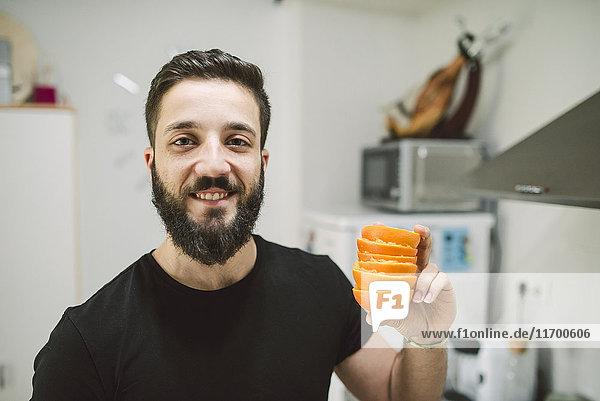 Lächelnder Mann mit Orangenschalen
