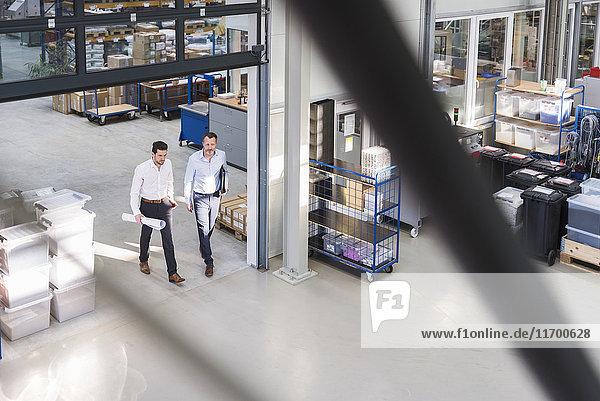 Zwei Geschäftsleute  die in der Fabrikhalle spazieren gehen.
