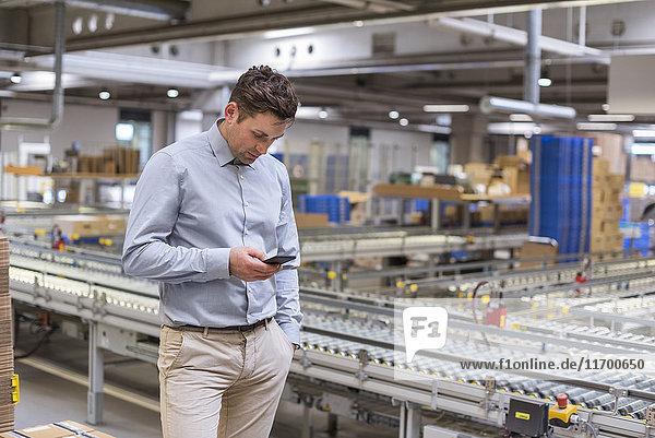 Mann am Förderband in der Fabrik beim Blick auf das Handy
