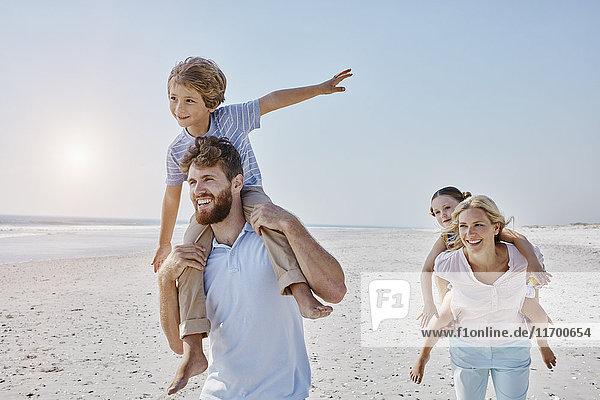 Fröhlicher Familienspaziergang am Strand