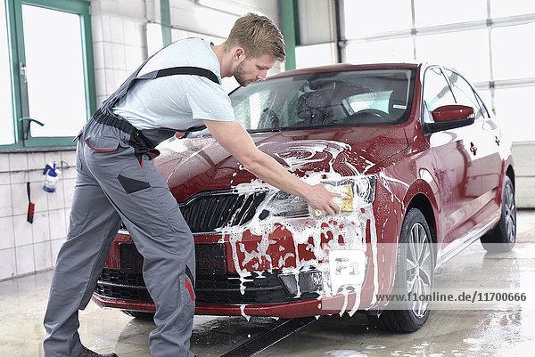 Mann reinigt Auto bei der Autowäsche