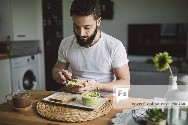 Junger Mann beim Frühstück zu Hause  Toast mit Avocadocreme