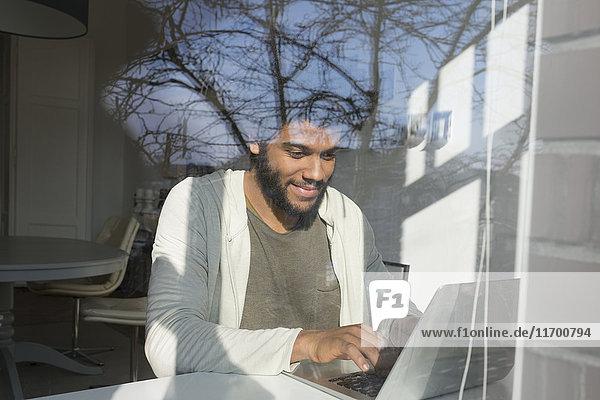 Mann arbeitet am Fenster zu Hause mit Laptop