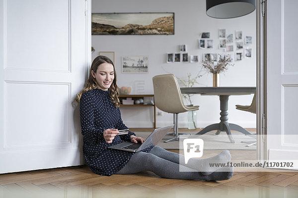 Lächelnde Frau zu Hause auf dem Boden sitzend mit Laptop im Türrahmen mit Kreditkarte