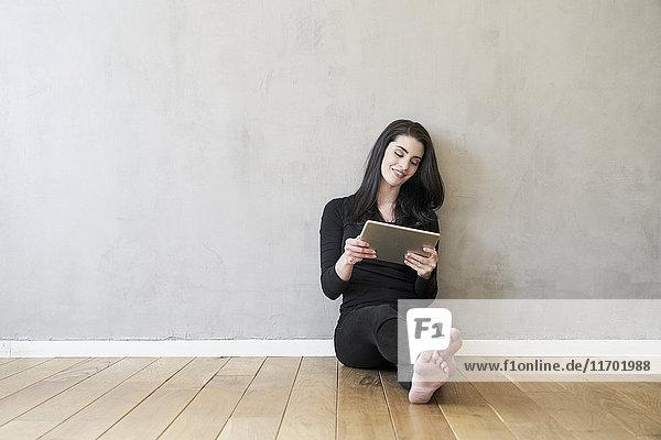 Lächelnde junge Frau auf dem Boden sitzend mit Tablette