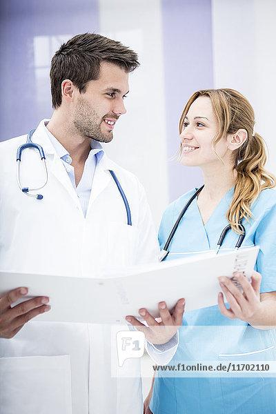 Zwei lächelnde Ärzte halten Mappe