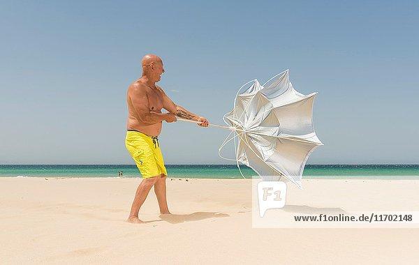 Man with sun umbrella on a windy day. Tarifa  Costa de la Luz  Cadiz  Andalusia  Spain.