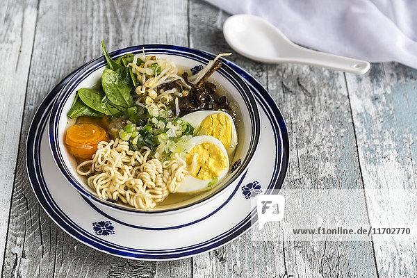 Bowl of ramen soup with spinach  carrot  boiled egg  bamboo sprouts and mushrooms