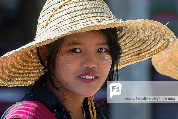 A portrait of a young woman wearing a straw hat on the market in the village of Khaung Tai on Inle Lake in Myanmar.