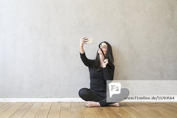 Junge Frau sitzt auf dem Boden und nimmt einen Selfie.