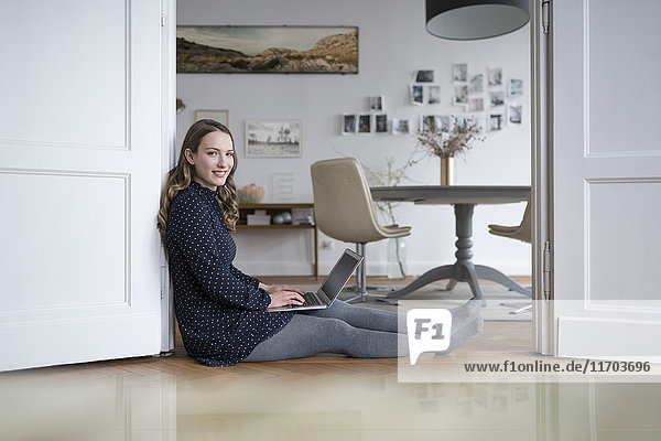 Smiling woman at home sitting on floor working with laptop in door frame