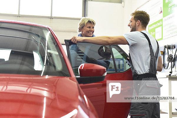 Kfz-Mechaniker mit Kunde in der Werkstatt am Auto