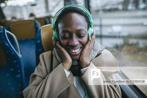 Fröhliche junge Frau beim Musikhören im Bus