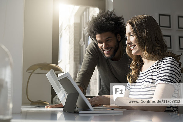 Lächelndes Paar arbeitet zu Hause mit Laptop und Tablett