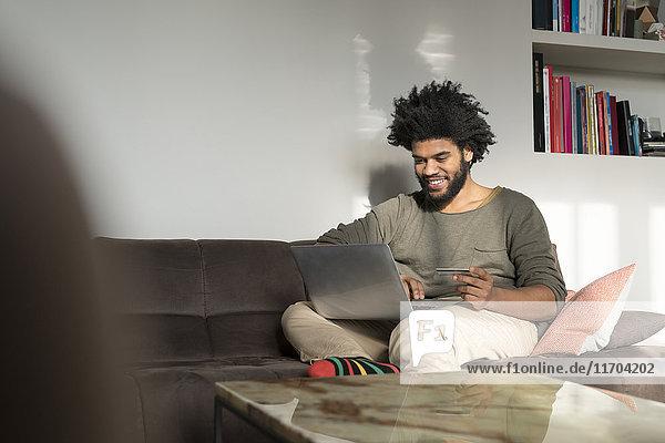Mann sitzt auf der Couch im Wohnzimmer mit Laptop und Kreditkarte