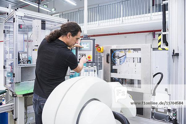 Mann bedient Montageroboter in der Fabrik