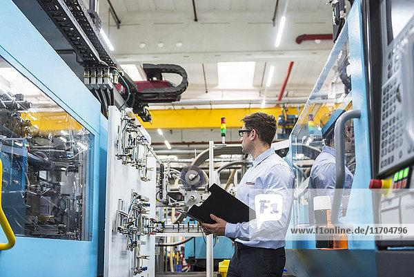 Mann mit Dokumenten zwischen den Maschinen in der Fabrikhalle