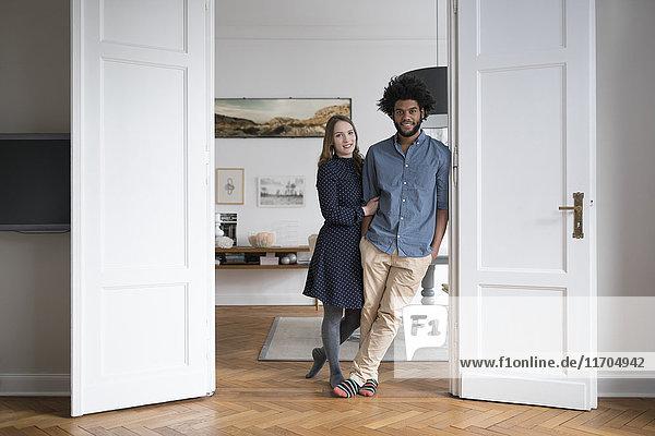 Lächelndes Paar zu Hause im Türrahmen stehend