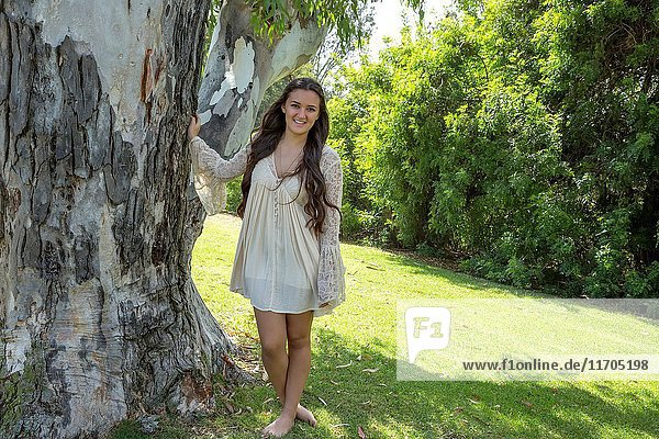 Teenage girl standing by a tree in San Diego  California.