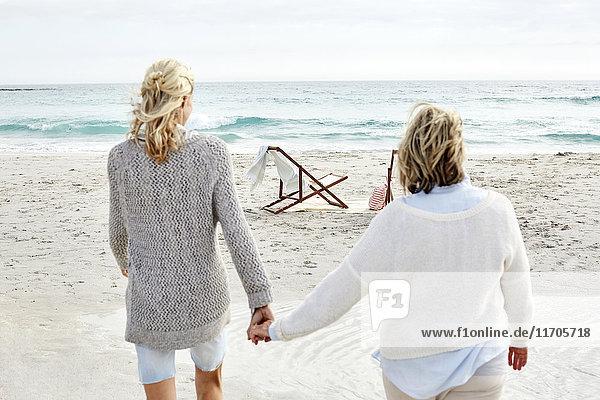 Mutter und Tochter gehen am Strand und halten sich an den Händen.