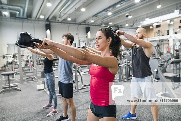 Gruppe von Athleten  die mit Kettlebells in der Turnhalle trainieren