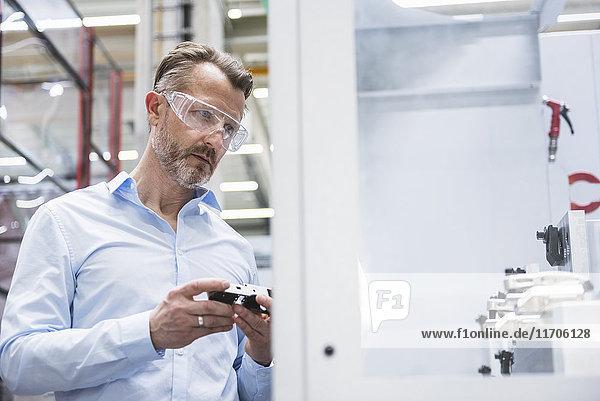 Mann mit Schutzbrille in der Fabrikhalle