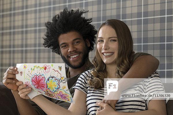 Lächelndes Paar auf der Couch sitzend mit Kinderzeichnung