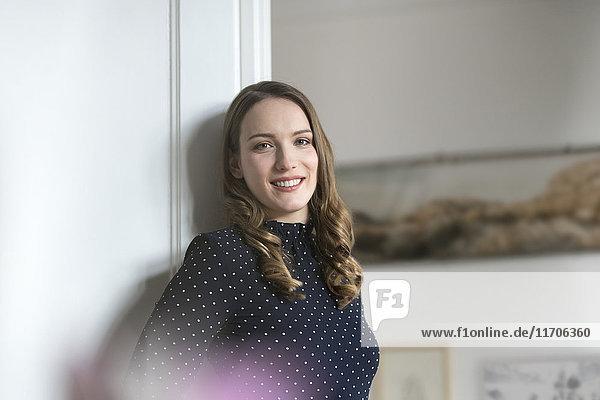 Lächelnde Frau zu Hause lehnt sich in den Türrahmen und schaut auf die Kamera.