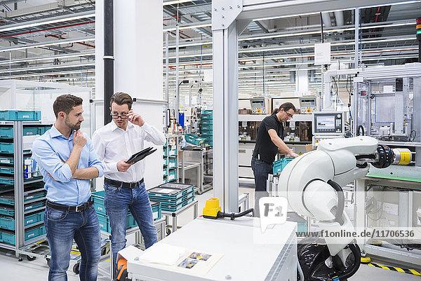 Mann  der den Montageroboter in der Fabrik bedient und zwei Männer  die sich unterhalten