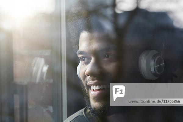 Mann am Fenster mit Blick nach draußen und Musik hören mit Kopfhörern