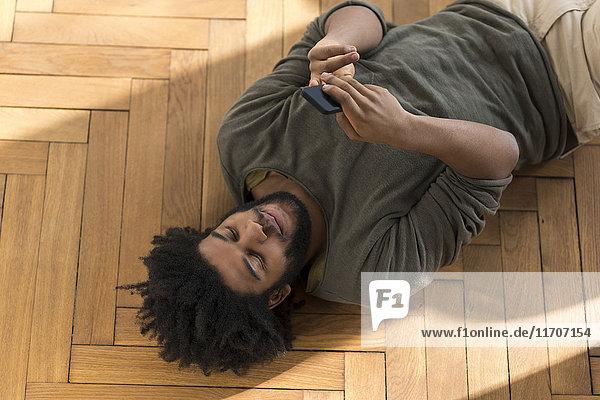 Mann auf dem Boden liegend mit Smartphone