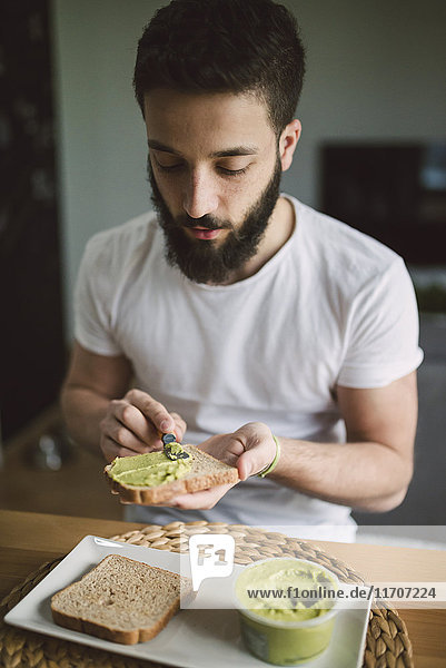 Young man having breakfast at home  toast with avocado cream