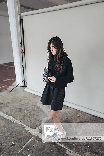 Junge Frau in flauschigen Pantoffeln mit Vintage-Kamera im Studio