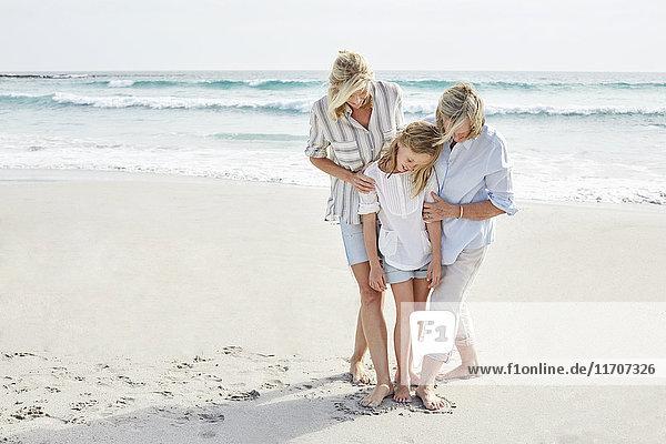 Mutter  Tochter und Großmutter in einem Herzen stehend  in den Sand am Strand gezogen