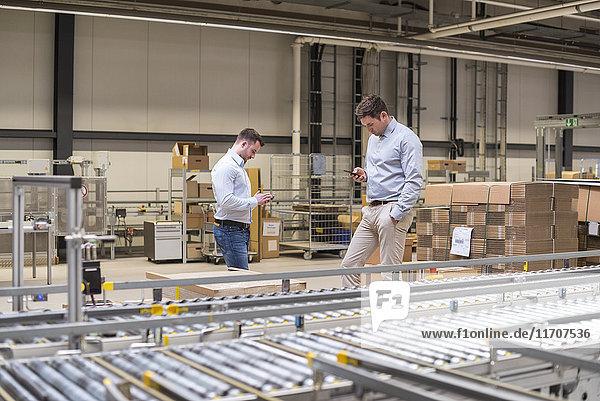 Zwei Männer auf dem Förderband in der Fabrik sehen sich Handys an.