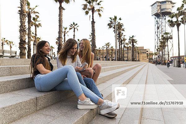 Spanien  Barcelona  drei glückliche junge Frauen auf der Treppe sitzen und Spaß haben