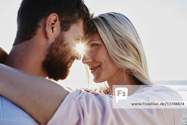 Lächelndes Paar  das sich bei Sonnenuntergang am Strand umarmt.