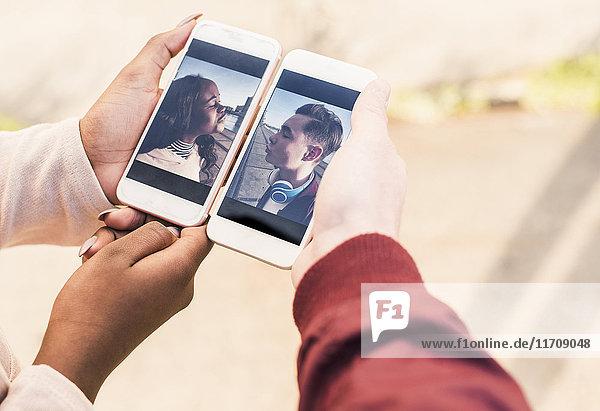 Hände halten Smartphones mit Bildern eines jungen Paares