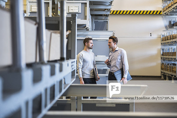 Zwei Männer  die im Fabriklager reden.