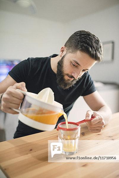 Junger Mann macht frischen Orangensaft
