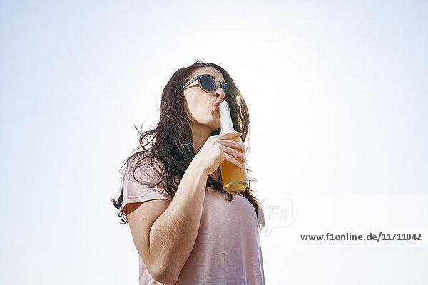 Junge Frau bei einem Bier unter blauem Himmel