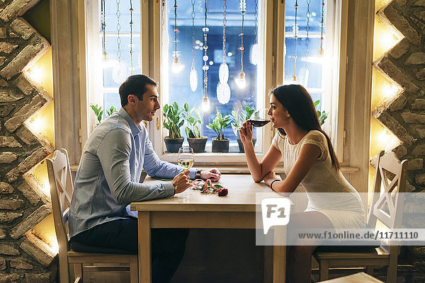 Junges Paar trinkt Wein in einem Restaurant am Valentinstag