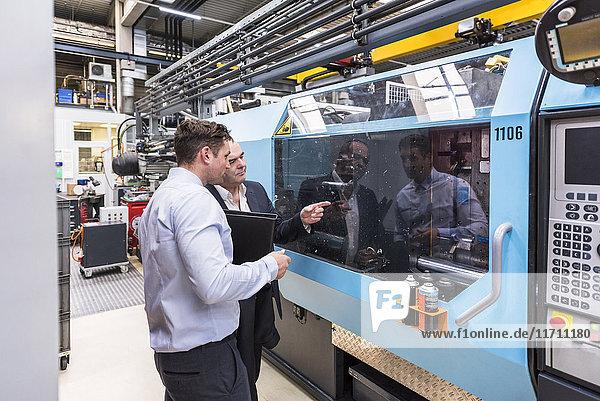 Zwei Männer reden über Maschinen in der Fabrikhalle