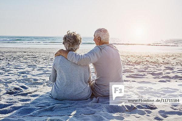 Seniorenpaar sitzt am Strand und schaut in die Ferne.