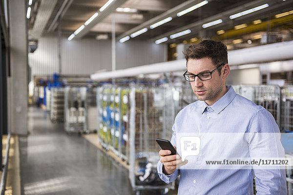 Geschäftsmann in der Fabrikhalle mit Blick auf das Handy