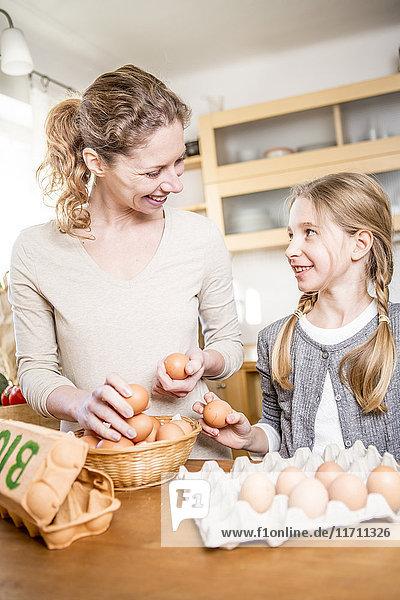 Mutter und Tochter mit Eiern in der Küche