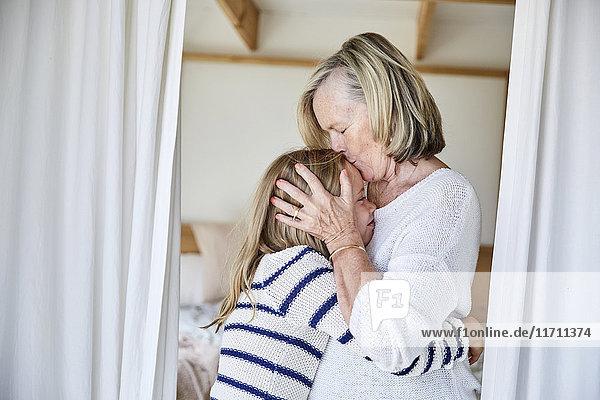 Großmutter beim Küssen ihrer Enkelin