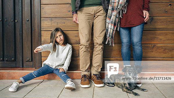 Mädchen mit Eltern und Hund an der Holzwand gestikulierend Mädchen mit Eltern und Hund an der Holzwand gestikulierend